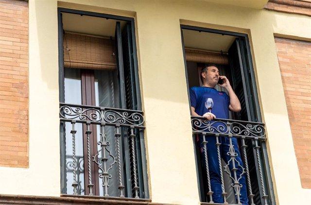 Un vecino de Triana asomado al balcón de su casa con una copa de vino  el día 34 del estado de alarma. Sevilla a 17 de abril del 2020