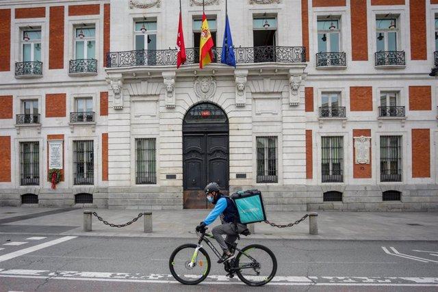 Un 'rider' de Deliveroo circula por la Puerta del Sol, en Madrid (España) a 19 de abril de 2020.