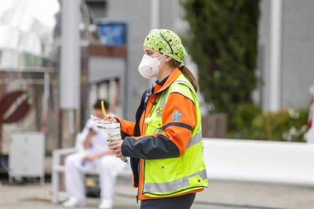Una trabajadora sanitaria protegida con mascarilla sostiene un tentempié en las inmediaciones del Hospital de Campaña de IFEMA donde trabajan a destajo para cuidar de todas personas con Covid-19 que están ingresadas en el recinto.