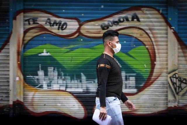 Un hombre ataviado con una mascarilla camina por una de las calles del centro de Bogotá, Colombia.