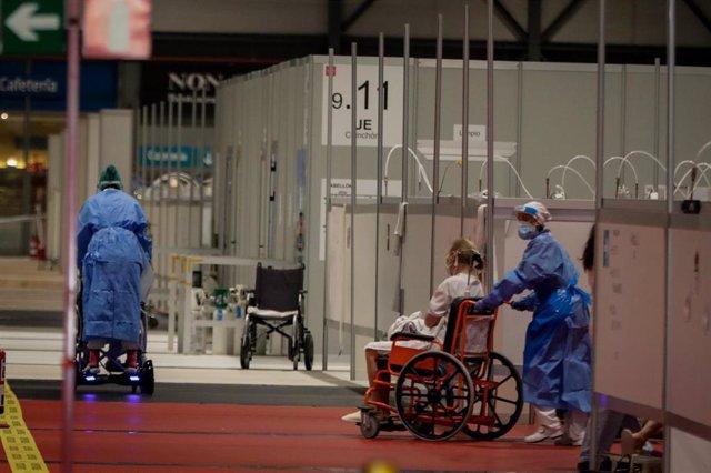 Dos sanitarios trabajan trasladando pacientes en silla de ruedas en el Pabellón 9 del hospital de campaña de Ifema.