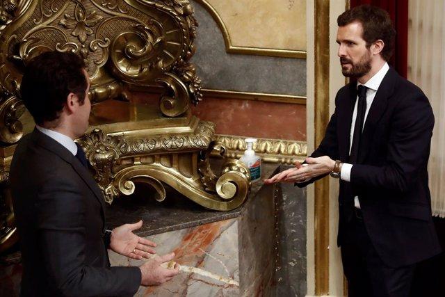 El líder del PP, Pablo Casado (d), y el secretario general del PP, Teodoro García Egea (i), desinfectan sus manos  durante el pleno celebrado este jueves en el Congreso de los Diputados para aprobar una nueva prórroga del estado de alarma,