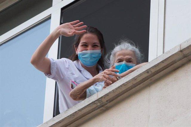 Una sanitaria ayuda a una paciente mayor a salir a la ventana para rendir homenaje a los sanitarios en el Hospital Fundación Jimenez Diaz