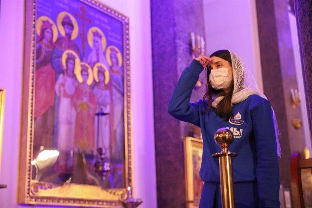 Una mujer con mascarilla en una catedral ortodoxa en San Petersburgo