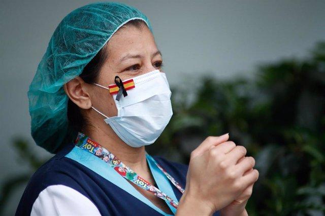 Una sanitaria, con una mascarilla que muestra una bandera de España con un lazo negro de luto por los fallecidos por coronavirus, aplaude en agradecimiento por el homenaje a los Sanitarios del Hospital Fundación Jiménez Díaz celebrado durante la pandemia