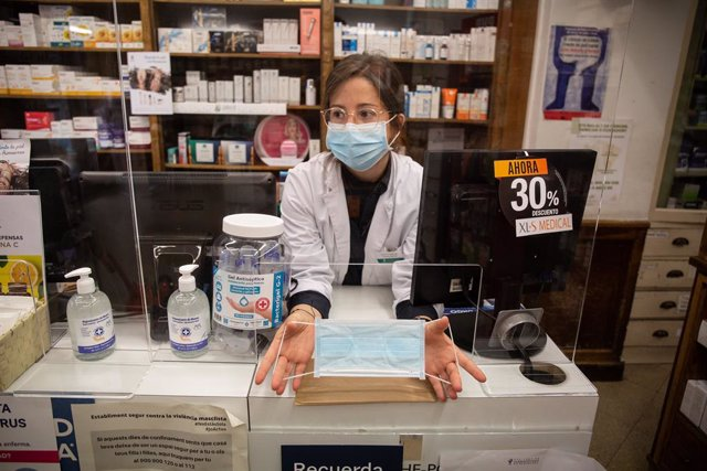 Una farmacèutica mostra una de les mascarillas que la Generalitat ha començat avui a repartir a la població dins d'una primera tanda d'1,5 milions d'unitats.