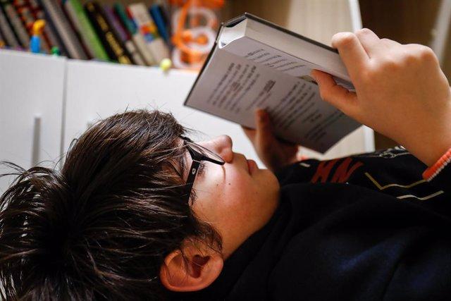 Un niño lee en su cuarto cuando queda tan solo una semana para que niños y preadolescentes puedan salir a la calle durante el confinamiento por el coronavirus, en Valdemoro/Madrid (España) a 20 de abril de 2020.