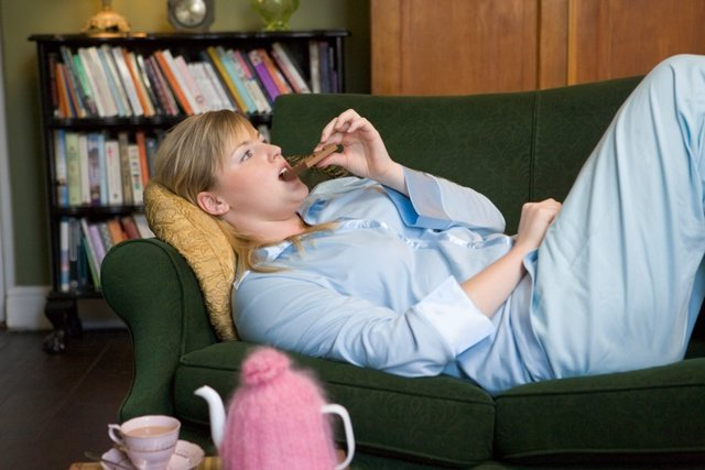 A young woman lying on her couch eating chocolate  Mujer joven tumbada en su sofá mientras come chocolate