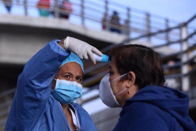 Un sanitario mide la temperatura de una presona en Colombia.