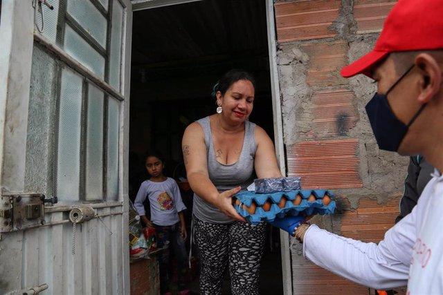 Un miembro de la Policía Militar entrega alimentos a una mujer durante un toque de queda impuesto para combatir la propagación del coronavirus en Bogotá, Colombia.
