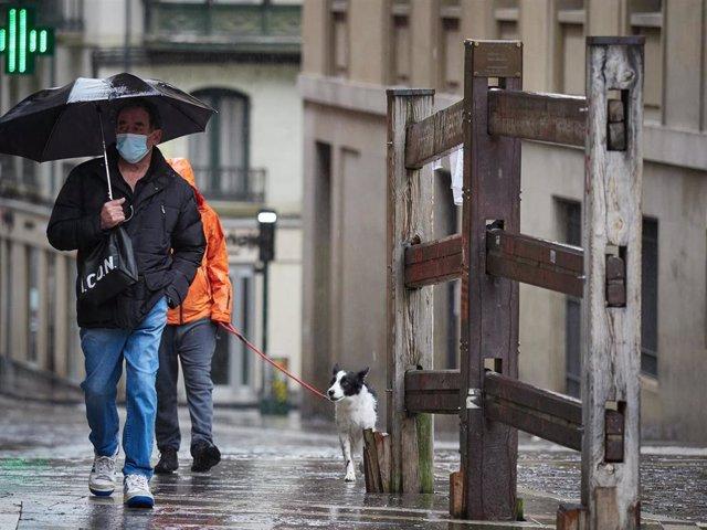Un hombre con mascarilla camina bajo la lluvia junto al vallado permanente del encierro de Pamplona de la cuesta de Santo Domingo