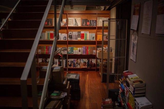 Llibres i material col·locat en les prestatgeries de la llibreria Laie Pau Claris llibreria-cafè situada al carrer català de Pau Claris, on els treballadors preparen llibres i material abans d'enviar-los. El local, que roman tancat al públic per la
