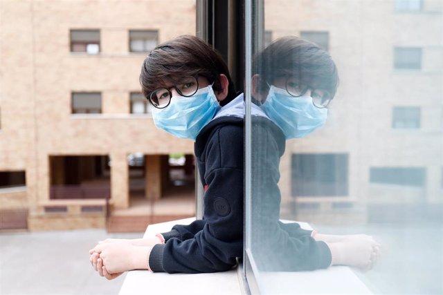 Un niño con una mascarilla se asoma a la ventana de su casa durante el confinamiento por el coronavirus, en Valdemoro/Madrid (España) a 20 de abril de 2020.