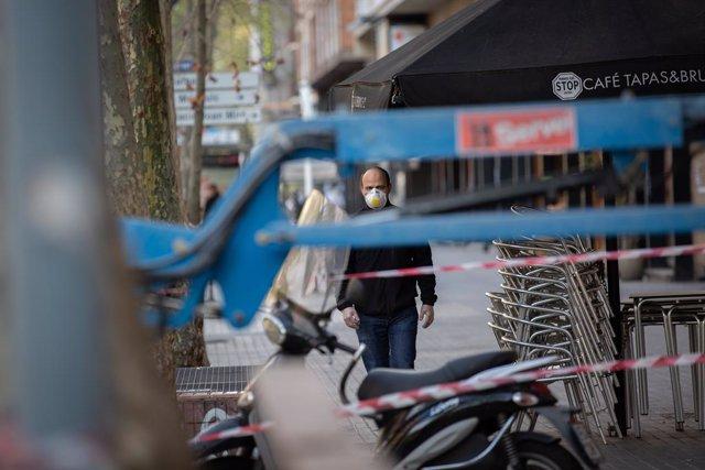 Un home protegit amb una mascarilla camina prop d'una obra durant el novè dia laborable des que es va decretar l'estat d'alarma al país a conseqüència del coronavirus, a Barcelona/Catalunya (Espanya) a 26 de març de 2020.
