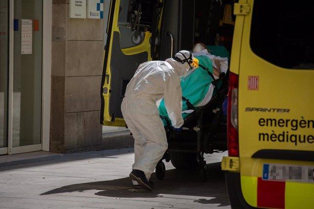 Un sanitari protegit amb un vestit puja a una persona contagiada amb coronavirus a una ambulància al Centre d'Emergències d'Atenció Primària Pere Camps en el Raval, a Barcelona/Catalunya (Espanya) a 6 d'abril de 2020.