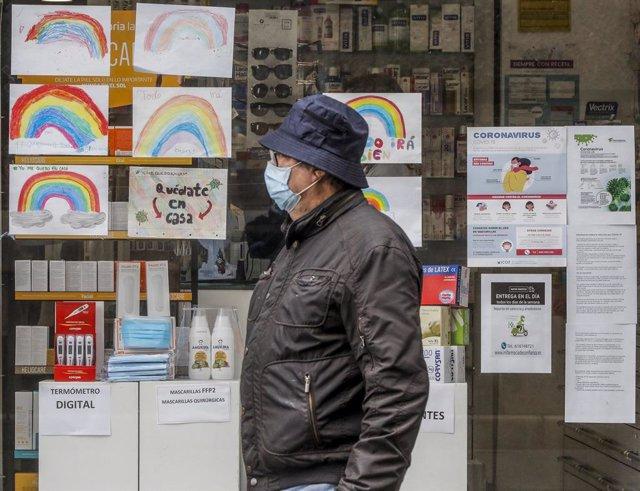 Un home amb màscara passa al costat d'una farmàcia durant el repartiment de màscares gratuïtes contra la covid-19 a gent gran i col·lectius de risc a la Comunitat Valenciana