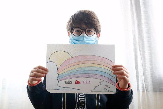 Un niño con mascarilla enseña un dibujo que ha hecho de un arcoiris y la frase 'Todo irá bien' cuando queda tan solo una semana para que niños y preadolescentes puedan salir a la calle