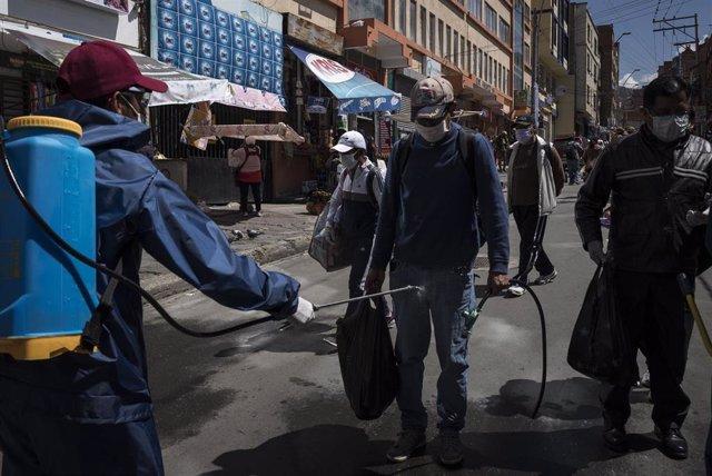 Un hombre es desinfectado antes de entrar a un mercado en la ciudad de La Paz, Bolivia.