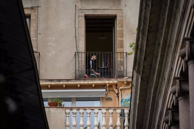 Un joven utiliza su ordenador portátil en su terraza durante el segundo día laborable del estado de alarma por el coronavirus, en Barcelona (España), a 17 de marzo de 2020.