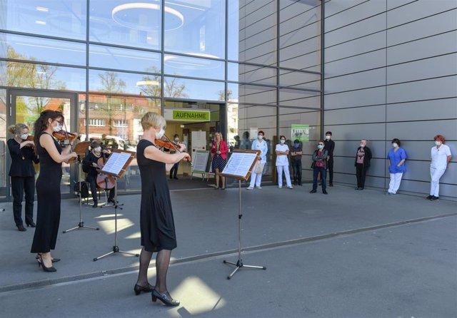 Músicos del teatro estatal de Cottbus dan un concierto en la entrada de un hospital