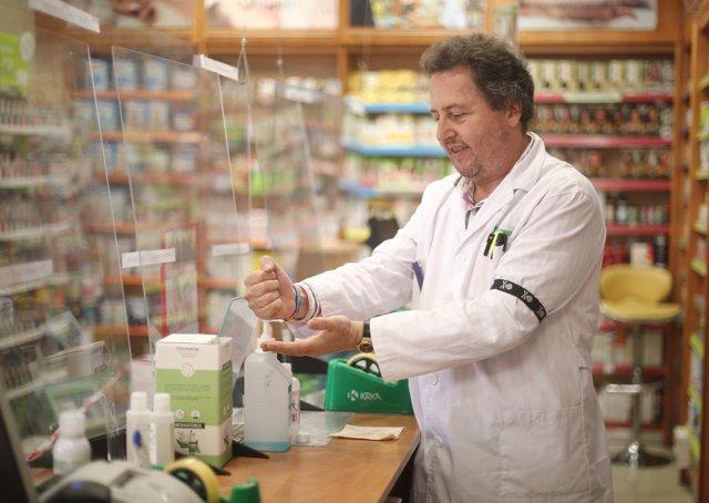 Un farmacéutico se desinfecta las manos el día en que el Boletín Oficial del Estado (BOE) publica el acuerdo de la Comisión Interministerial de Precios de los Medicamentos.