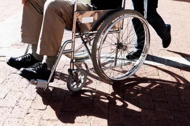 Man in a wheelchair is pushed across parking lot