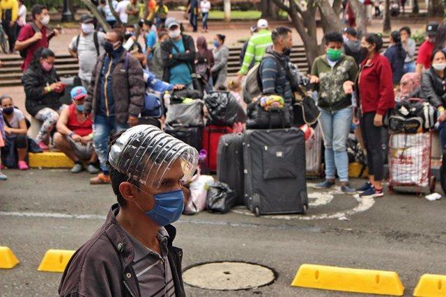 Migrantes venezolanos esperan un autobús que les lleve a la frontera en plena pandemia de coronavirus
