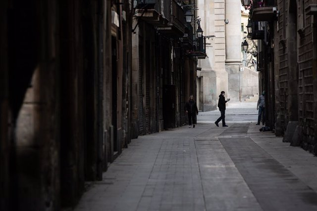 Una persona camina per un carrer de Barcelona durant el tercer dia laborable de l'estat d'alarma per coronavirus, a Barcelona