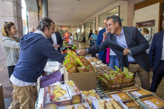 El consejero de Industria y Comercio, en un puesto de un mercado en Torrelavega
