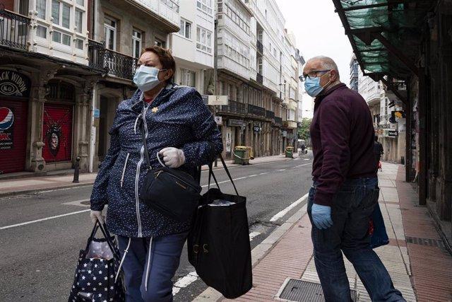 Transeúntes pasean con mascarillas por A Coruña en el día 41 del estado de alarma por la crisis sanitaria del Covid-19 donde tan solo están permitidos por el momento los desplazamientos para empleados de servicios esenciales, aquellos que no puedan tele
