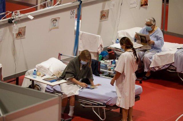Varios pacientes en el Pabellón 9 del hospital de campaña de IFEMA, en el que los pacientes de coronavirus son ahora atendidos únicamente en el Pabellón 9 tras el cierre del 7 al bajar la presión asistencial y que estará operativo previsiblemente hasta fi