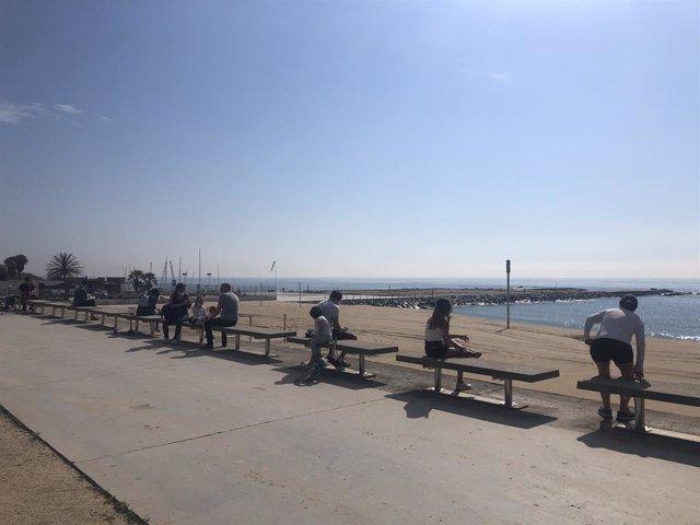 Adults i nens mantenen la distància de seguretat en una platja de Barcelona, en el primer dia en el qual es permet sortir a passejar amb els menors des de la declaració de l'estat d'alarma pel coronavirus.