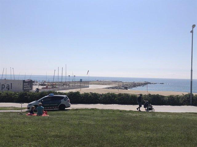 Adults passegen amb els seus fills prop d'una platja a Barcelona, en el primer dia en el qual es permet sortir als nens des de la declaració de l'estat d'alarma pel coronavirus.