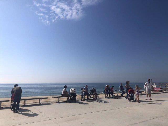 Famílies passegen prop d'una platja de Barcelona en el primer dia en què es permet sortir amb nens al carrer des de la declaració de l'estat d'alarma pel coronavirus.