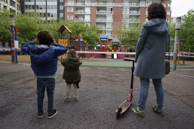 Un niño y una niña frente a un parque infantil clausurado, el primer día en el que los menores de 14 años pueden salir a la calle, en Bilbao (País Vasco/España) a 26 de abril de 2020.