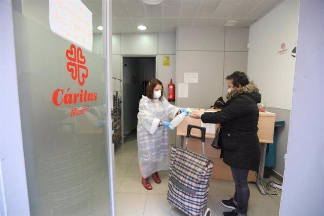 Una voluntaria hace cumplir a una mujer las normas de higiene en un economato solidario de Cáritas