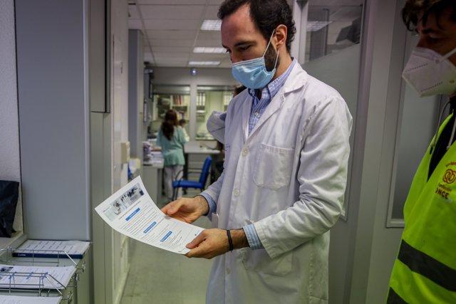 Un farmacéutico enseña una de las hojas con información del servicio farmacéutico del Hospital Gregorio Marañón, en Madrid (España) a 27 de abril de 2020.