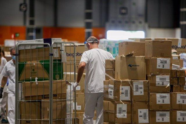 Trabajadores sanitarios protegidos con mascarilla mueven cajas en el interior del almacén habilitado en el hospital provisional de IFEMA para pacientes con Covid-19.