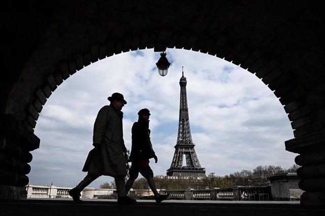 Dues persones passejant prop de la Torre Eiffel de París