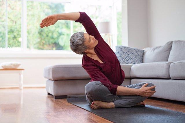 Mujer mayor haciendo yoga en casa.