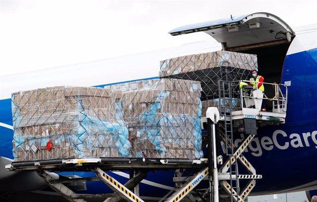 Trabajadores del aeropuerto bajan el material sanitario comprado por la Comunidad de Madrid de uno de los aviones procedentes de China.