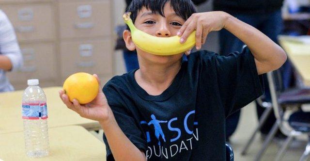 Un niño beneficiario de las actividades de la Gasol Foundation juega con dos piezas de fruta