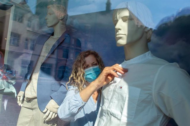 Dorothee Hahn, a visual marketing designer for the Ramelow fashion house, wears a face mask as she dresses a Mannequin. Most of the shops across the country had been closed in recent weeks due to the nationwide spread of the coronavirus.