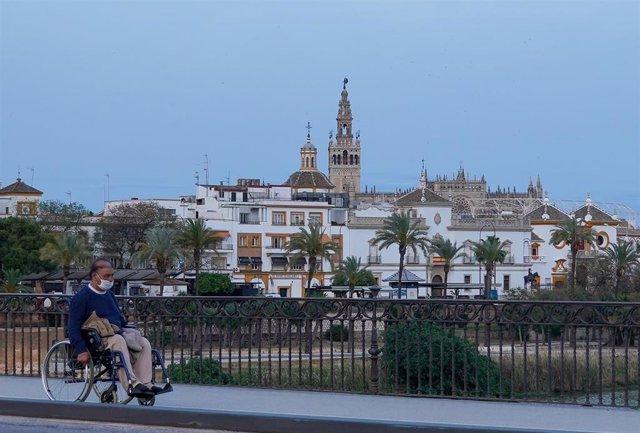 Un ciudadano en silla de ruedas por el Puente de Triana casi desértico a los 40 días de estado de alarma en Sevilla a 23 abril del 2020