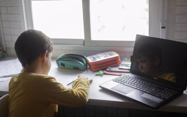 Un niño estudia y hace los deberes en su casa de Madrid durante el confinamiento.