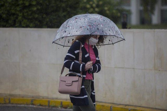 Una mujer con paraguas y mascarilla, durante la alerta amarilla por lluvia