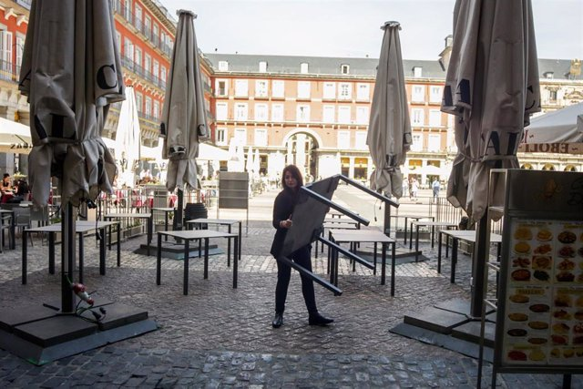 Varios empleados de un bar de la Plaza Mayor de Madrid recogen la terraza un día antes de que se cierre toda la hostelería