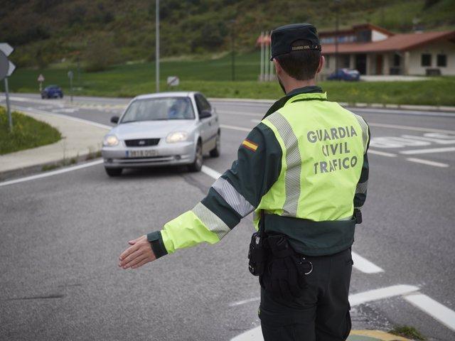 Un agente de la Guardia Civil de Tráfico manda parar a un vehículo en un control policial durante el día 32 del estado de alarma