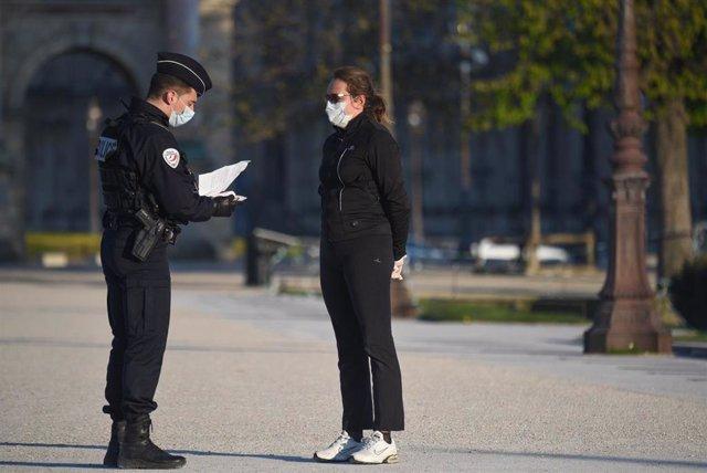 Policía de Francia comprueba el permiso de desplazamiento de una mujer durante el confinamiento a causa de la pandemia de coronavirus