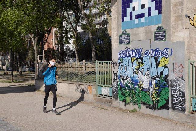 Un hombre con mascarilla junto a un graffitti de coronavirus en París